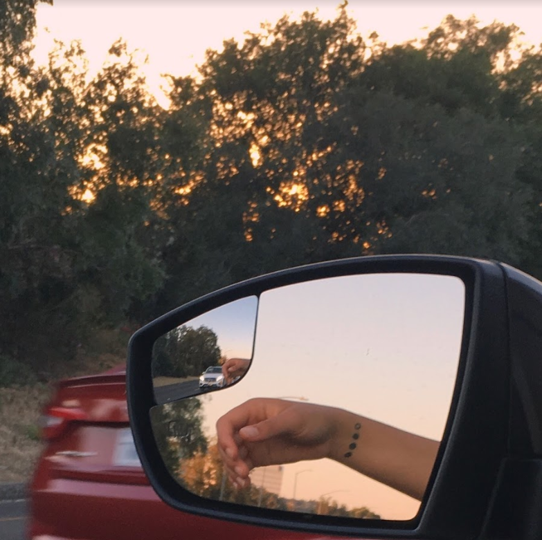 Reflection in car side mirror of an arm hanging out the window